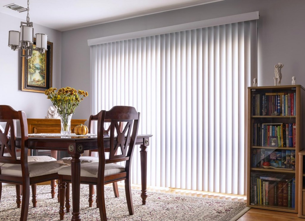 A shine through the vertical blinds to the dining area with brown table and chairs along with booksehlves