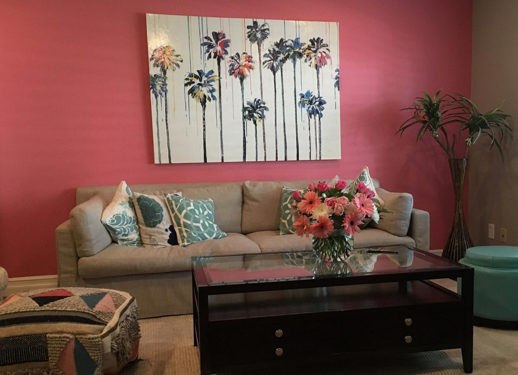A living room with coral Pink color painted wall with couch and pattern pillows on top and flowers setting top of glass of table