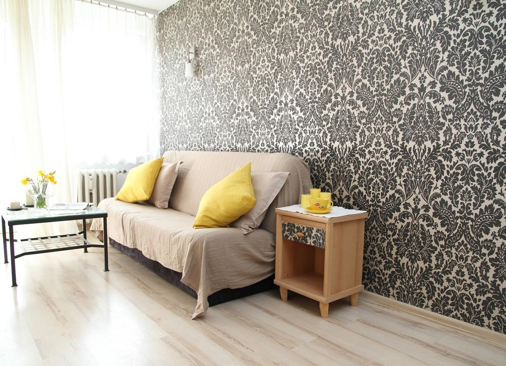 A modern interior living room decorated with black and white ornamental pattern wallpaper and light beige couch