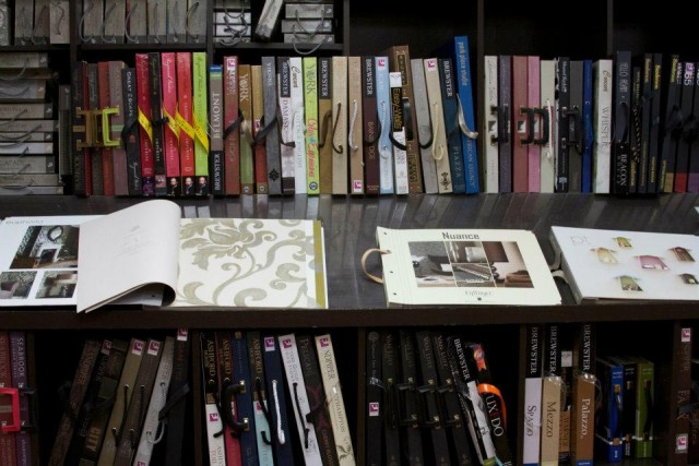 A brochures for interior style in pattern and colour displayed on the bookshelves and on the table with open books