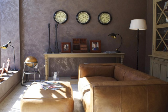 A living room decorated with vintage ornaments and brown leather couch and lightly scraped pattern wallpaper