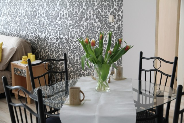 black and white pattern wallpaper close up of dining table with white table runner with tulips and mugs