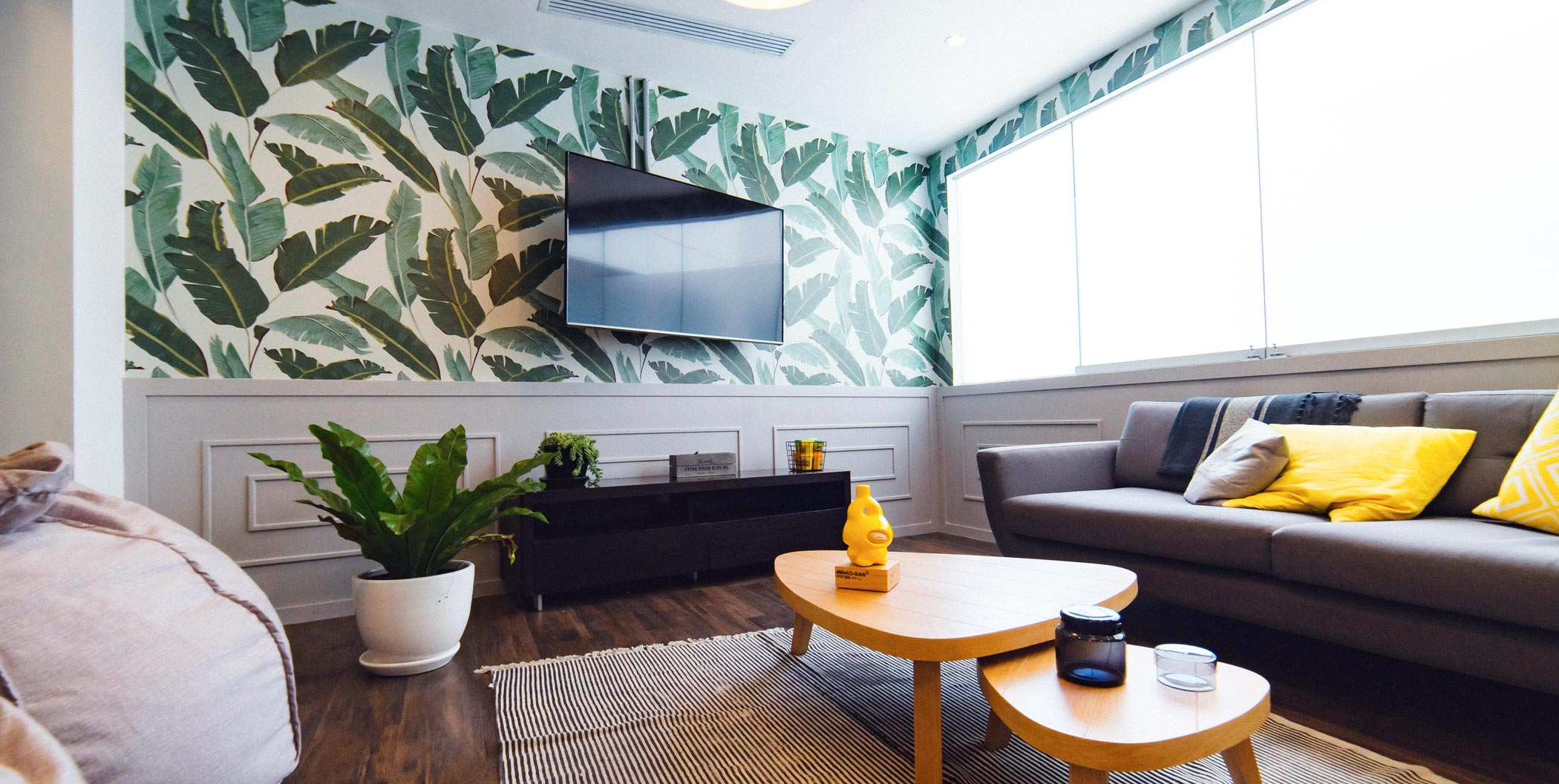 A modern living room with green leafs pattern wallpaper and mounted tv with grey two person couch