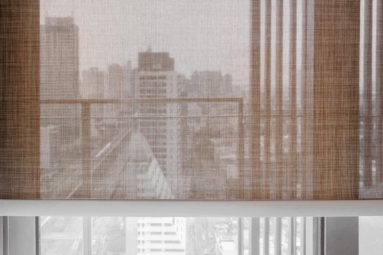 A textural light beige color roller shades covers the window from the city view