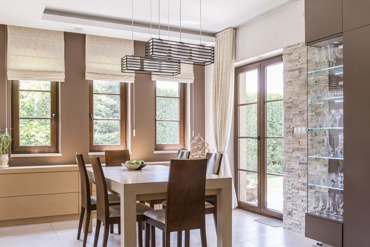 A modern dining room interior with beige vignette roman shades on the window along the balcony door and dining tables