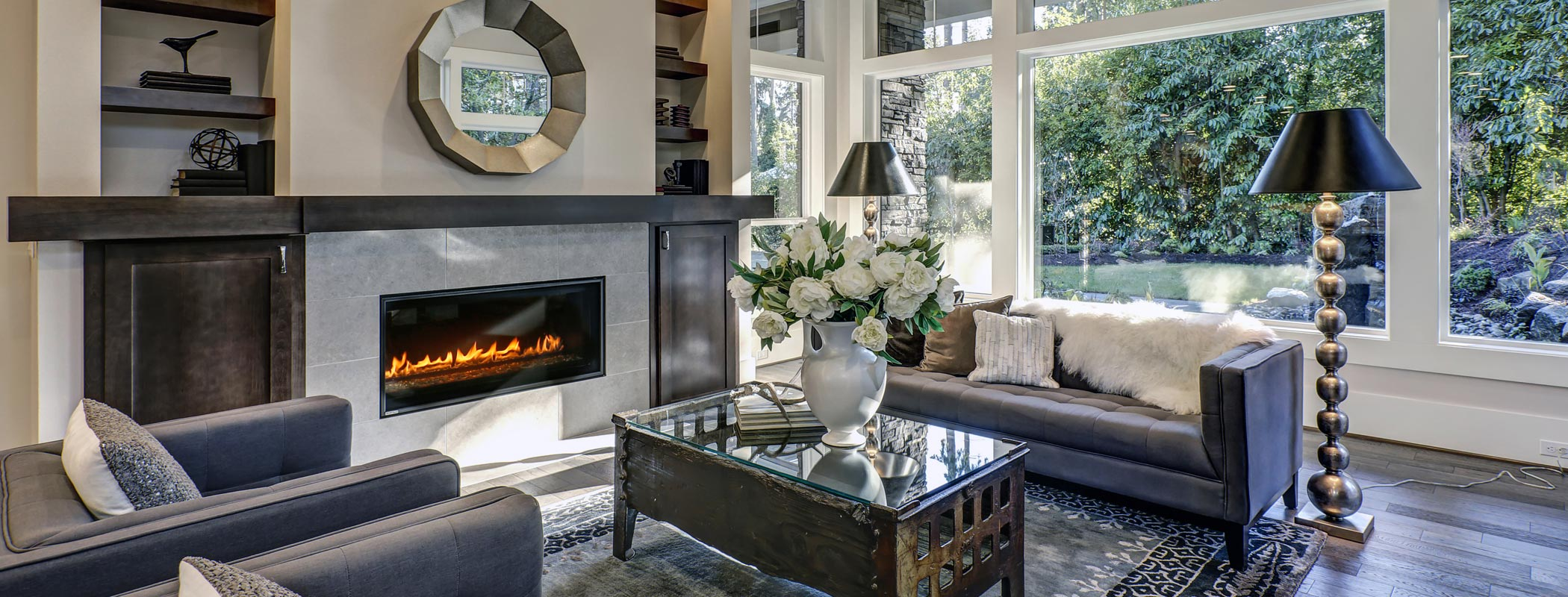 A luxurious living room interior with modern fireplace installed on the wall and black leather couches and wide open windows with the view of greenery garden
